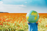 Pre-adolescent boy holding globe in poppy field against blue sky - MJ02394