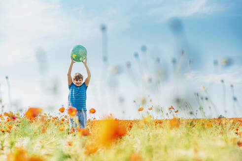 Happy boy holding globe while standing in poppy field against sky on sunny day - MJF02397