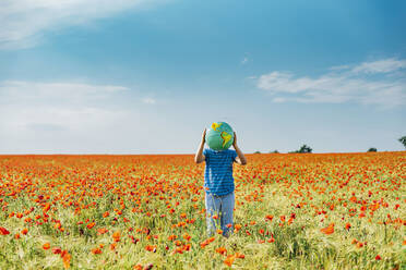 Pre-adolescent boy holding globe while standing in poppy field against blue sky - MJF02400