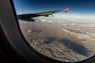 Aircraft wing flying over desert seen through window - NGF00520