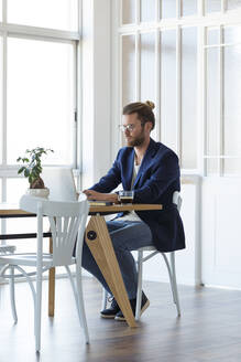 Businessman using laptop at table in modern office - JSRF00450