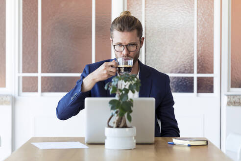 Businessman with laptop and cup of coffee at table - JSRF00456