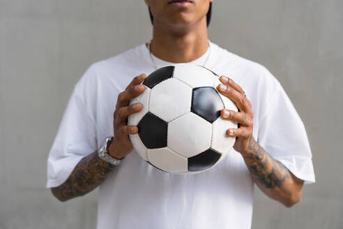 Young man's hands holding football, close-up - MGIF00563