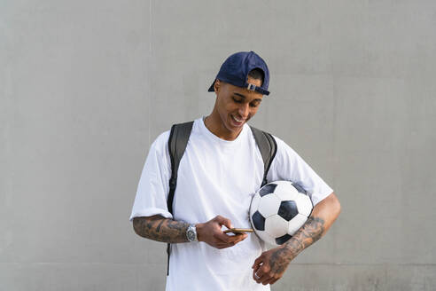 Tattooed young man with football alooking at smartphone - MGIF00569