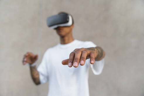 Hand of tattooed young man using Virtual Reality Glasses, close-up - MGIF00584
