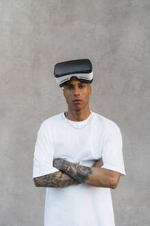 Portrait of tattooed young man withVirtual Reality Glasses - MGIF00587