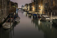 Boats moored in canal amidst buildings in Venice at night - LJF00461