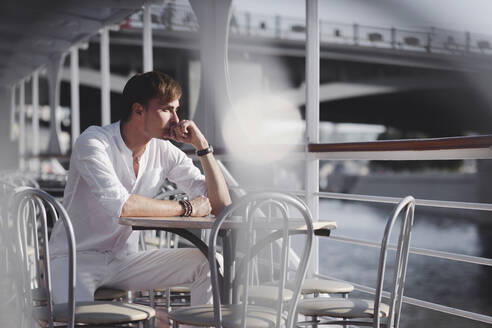 Pensive man wearing white clothes sitting on excursion boat at sunlight looking at distance, Moscow, Russia - EYAF00310