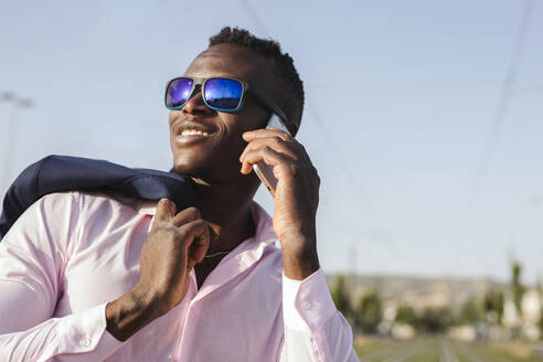 Young businessman with sunglasses using his smartphone outside - LJF00462