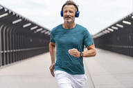 Sporty man wearing headphones and jogging - DIGF07493