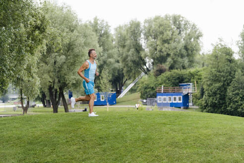 Sporty man jogging in a park - DIGF07499