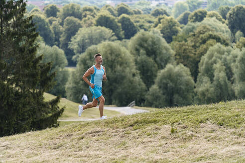 Sporty man jogging in a park - DIGF07502