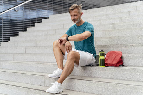 Sporty man checking his smartwatch - DIGF07517