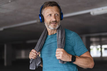 Sporty man wearing headphones after workout - DIGF07529