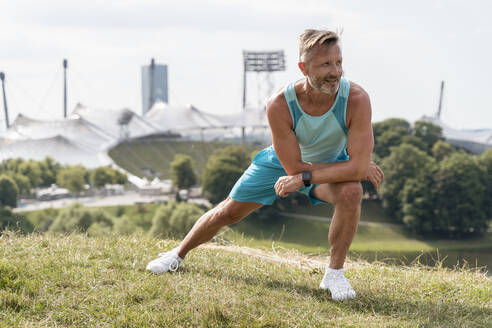 Sporty man stretching in a park - DIGF07547