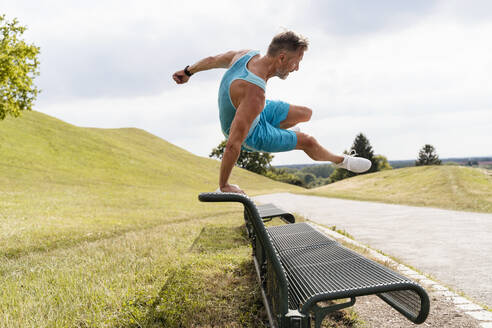 Sporty man jumping over a bench in a park - DIGF07550