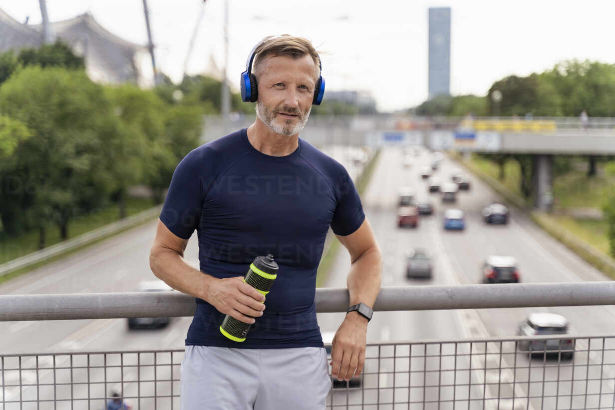 Sporty man with drinking bottle and headphones on a bridge - DIGF07553 - Daniel Ingold/Westend61