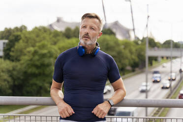 Sporty man with headphones standing on a bridge - DIGF07556