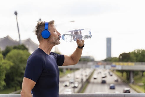 Sporty man wearing headphones and drinking water on a bridge - DIGF07559