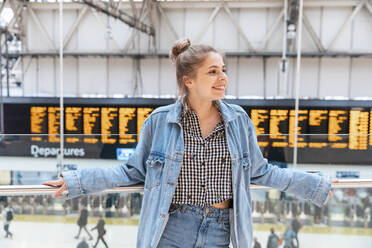 Portrait of happy young woman at train station, London, UK - WPEF01595