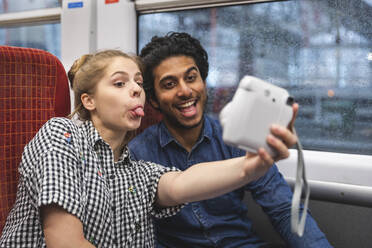 Portrait of friends having fun while taking selfie with instant camera in train, London, UK - WPEF01598