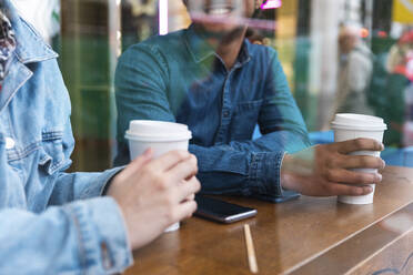 Hands holding disposable cups in a coffee shop, partial view - WPEF01610