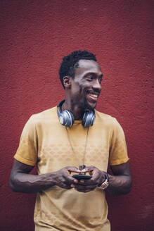 Handsome African man listening to music with headphones and mobile phone. It is located in the streets of Madrid, Spain. - OCMF00479