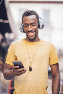 Portrait of smiling man listening music with headphones looking at smartphone - OCMF00491