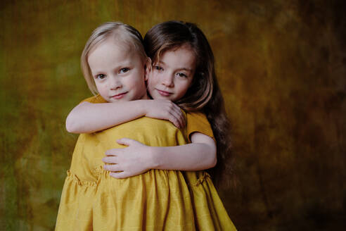 Portrait of smiling girl hugging her little sister - OGF00069