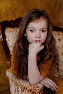 Portrait of little girl sitting on lounge chair - OGF00072