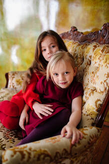 Portrait of two little sisters sitting together on lounge chair - OGF00075