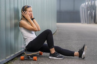 Smiling young woman sitting on longboard listening music with headphones - STSF02122