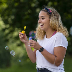Laughing blond woman making soap bubbles - STSF02125