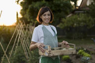 Woman with wooden box in garden - MAUF02696