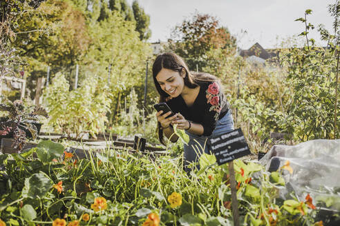 Happy young woman taking pictures with smartphone in urban garden - VGPF00049