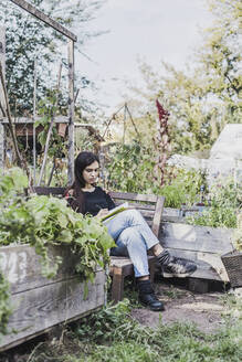 Young woman relaxing in urban garden - VGPF00058