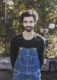 Portrait of smiling man wearing denim dungarees in garden - VGPF00061