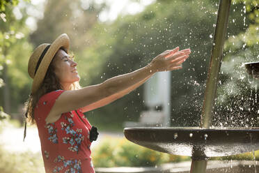 Smiling woman splashing with water of fountain in summer - FLLF00240