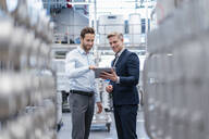 Two businessmen with tablet talking in a modern factory - DIGF07562