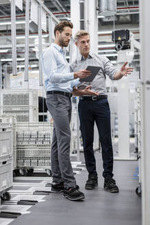 Two businessmen with tablet talking in a modern factory - DIGF07586