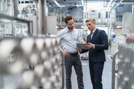Two businessmen with tablet talking in a modern factory - DIGF07646