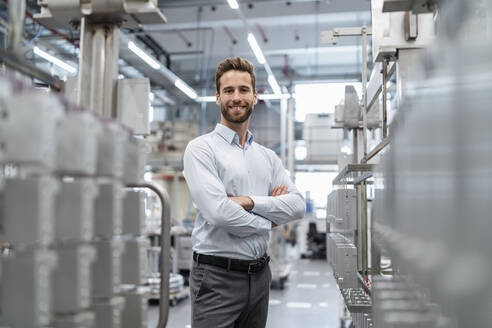 Portrait of a confident businessman in a modern factory - DIGF07649