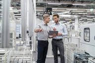 Two businessmen with tablet talking in a modern factory - DIGF07652
