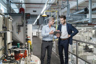 Two businessmen with tablet talking in a modern factory - DIGF07658