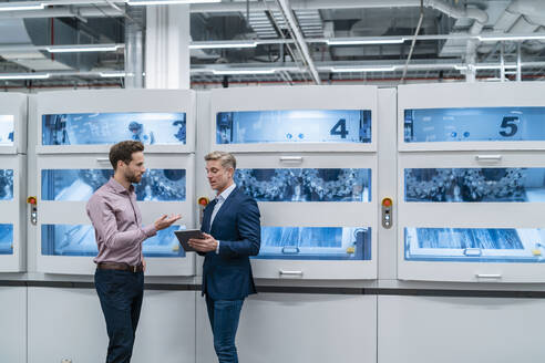 Two businessmen with tablet talking at machine in a modern factory - DIGF07679