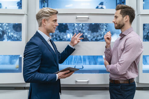 Two businessmen with tablet talking at machine in a modern factory - DIGF07682