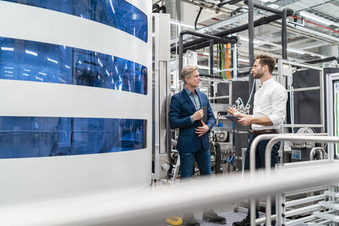 Two businessmen talking in a modern factory - DIGF07697