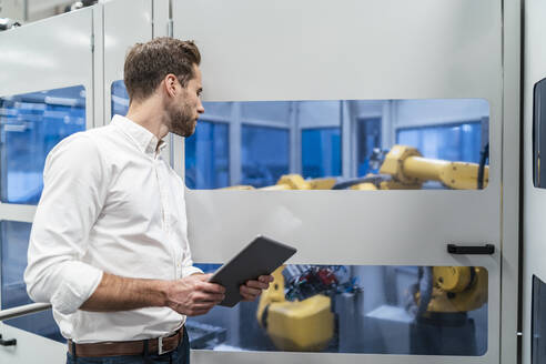 Businessman with tablet looking at robot in a modern factory - DIGF07703
