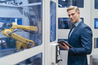 Portrait of a confident businessman in front of a robot in a modern factory - DIGF07706