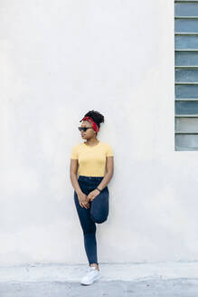 Young woman wearing hair-band and sunglasses leaning against white wall - SODF00001